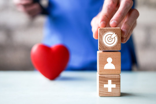 Concept of medical strategy and action plan. Businessman hand putting wood cube block on top with icon goal in health care.