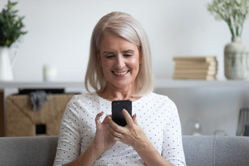 Smiling mature woman holding phone, using mobile device apps