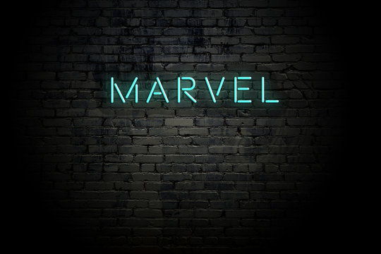 Highlighted brick wall with neon inscription marvel