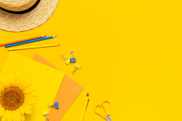 Fotomurales - Top view flat lay of workspace desk styled design with sunflowers, straw hat, notebook, diary, pencils, pen scissors on bright yellow background. Autumn or summer Concept. Sunflower natural background
