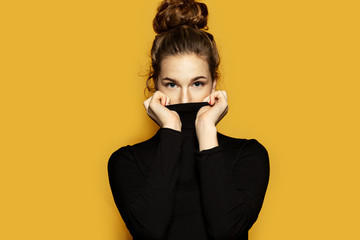 Portrait of beautiful woman wearing black trendy pullover. Fashionable picture of girl with tied up brunette hair posing on yellow background. Lifestyle and modern fashion concept
