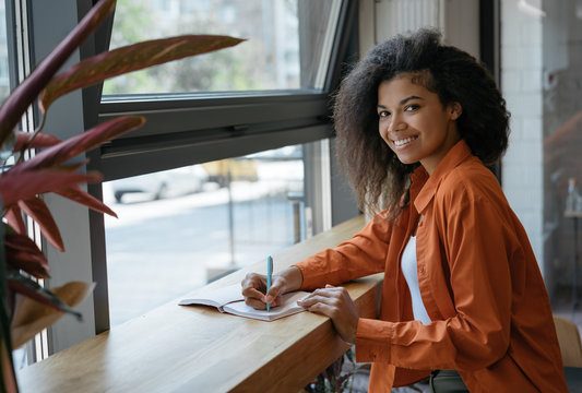 Student studying, learning language, exam preparation at modern library, education concept. Dark skinned business woman planning start up project, taking notes, working in office. Successful business