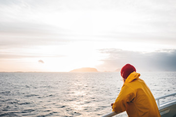 Young traveler wearing red hat and yellow raincoat floating on ship looking at sunset sea after storm and foggy mountains on skyline. Lifestyle travel, scandinavian authentic landscape.