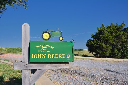 Calumet, Oklahoma - July 20, 2017: Metallic Mailbox with the colors and brand of John Deere along of countryside road in the state of Oklahoma. John Deere is an American manufacturer of agricultural,