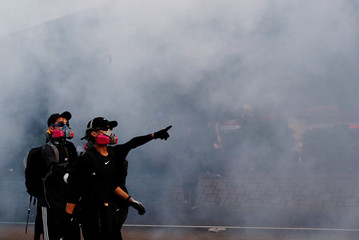 Anti-government protesters react from tear gas during a demonstration near Central Government Complex in Hong Kong