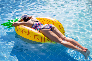 Woman swimming in the pool on inflatable pineapple