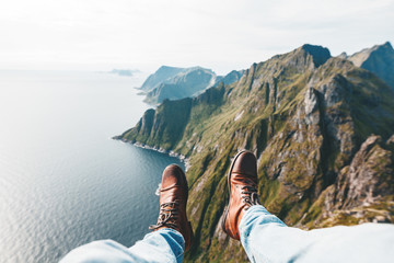 Close Up view on feet wearing hiking boots. Man tourist sitting on the edge cliff mountains above sea Wall mural