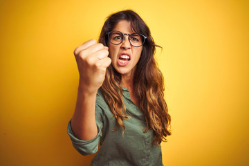 Young beautiful woman wearing green shirt and glasses over yelllow isolated background angry and mad raising fist frustrated and furious while shouting with anger. Rage and aggressive concept.