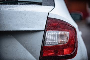 view of the rear of a white car with water drops after rain. Concept on the topic of polishing a car.