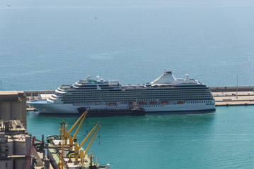 A cruise ship at the port area on the background of blue sea