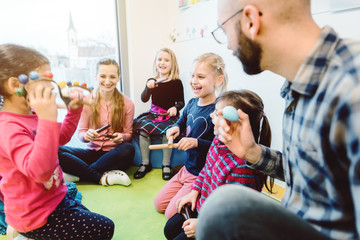 Preschool teachers and children making music