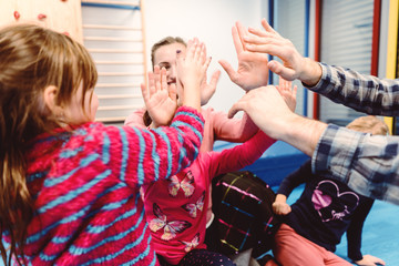 Children and teacher in kindergarten doing high-five after Sport