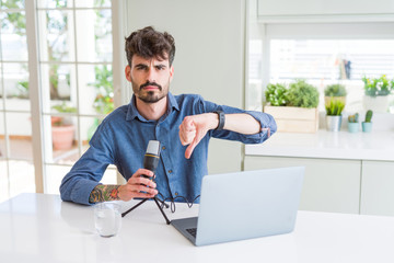 Young man recording podcast using microphone and laptop with angry face, negative sign showing dislike with thumbs down, rejection concept