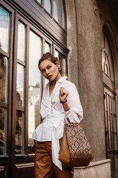 Outdoor fashion portrait of elegant, luxury woman wearing trendy white shirt, leather trousers, holding beige, brown reptile, snakeskin, python print bag, handbag, walking in street of European city