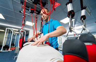 Physiotherapy. Suspension training therapy. Young man doing fitness traction therapy with suspension-based exercise training system.