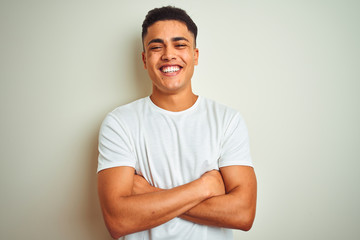 Young brazilian man wearing t-shirt standing over isolated white background happy face smiling with crossed arms looking at the camera. Positive person.