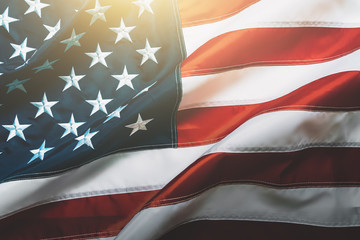 USA flag background. Waving American flag in sunlight flare, close up
