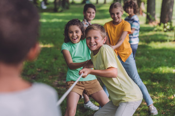 selective focus of cheerful kids competing in tug of war with african american boy