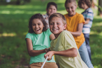 selective focus of happy kids competing in tug of war