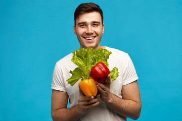 Happy unshaven young guy vegan with muscular fit body looking at camera with broad radiant smile carrying fresh colorful veggies and lettuce from grocery shop. Veganism, raw food and dieting