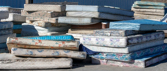 Dirty used mattresses piled at recycling site.