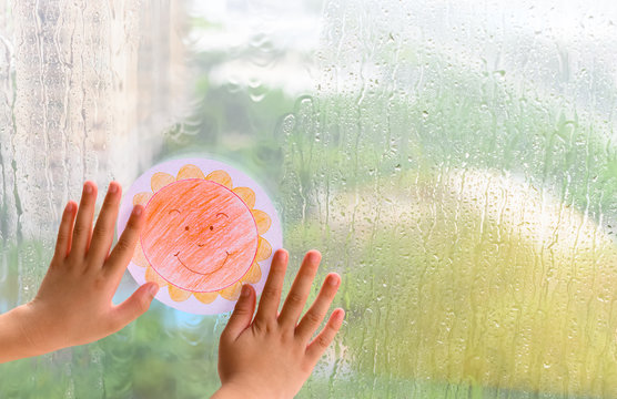 kid holding picture of a smiling sun in a raining day concept of faith and optimism
