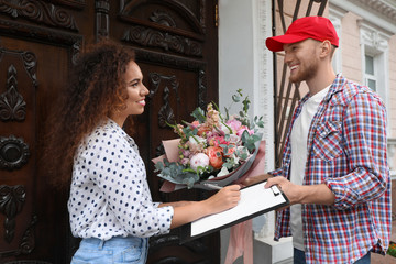 African-American woman receiving flower bouquet from delivery man at door