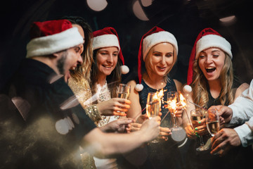 Christmas party. Celebration atmosphere. Friends dancing with champagne glasses and sparkles on New...