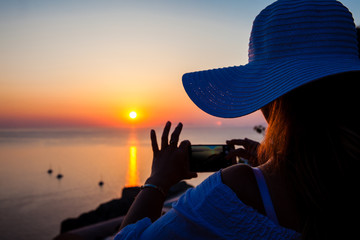 SANTORINI, GREECE - APRIL, 2018: Young woman taking pictures of the beautiful sunset at the famous Caldera of Santorini Island in Oia City