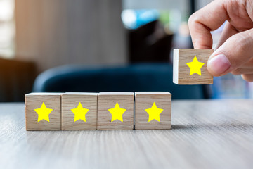 customer holding wooden blocks with the five star symbol. Customer reviews, feedback, rating, ranking and service concept.