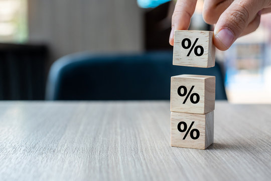 business man Hand putting wood cube block with percentage symbol icon. Interest rate,  financial, ranking and mortgage rates concept