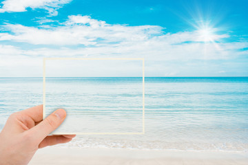 Summer Trip and Vacation Concept : Abstract image of Hand holding a picture of beautiful seascape view in summer time.