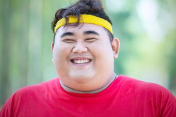 Smiling obese man wears sportswear in park