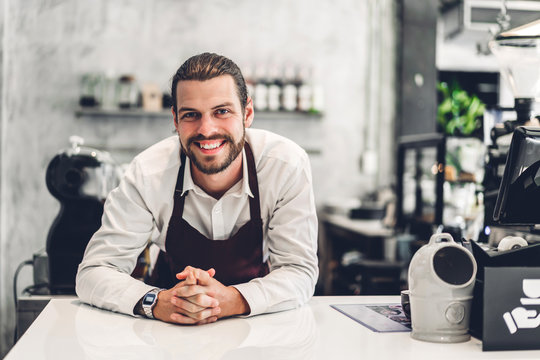 Portrait of handsome bearded barista man small business owner working behind the counter bar in a cafe