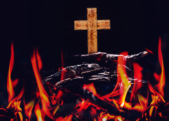 Close up of wooden cross on top of ashes and bonfire with black background, Christian Conceptual image, Easter background.