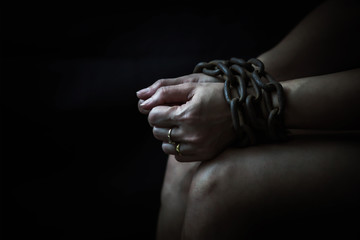 Close up of woman hands bondage with old rusty metal chain in the dark room, Conceptual image sex abuse and Slave trade prevention concept with copy space.
