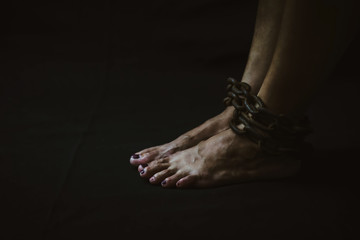 a women  bondage by metal chain to her legs sitting on the wooden floor in dark room, conceptual image with copy space