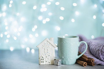 Creative image of hot chocolate with cream and cinnamon stick in a blue rustic ceramic cup. The concept of winter cozy holidays. Snow effect.