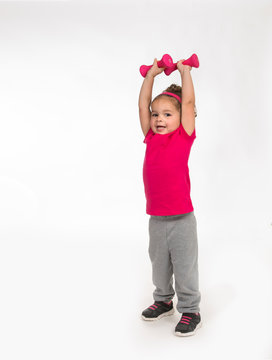 Mixed race toddler girl works out exercising lifting pink weights above her head