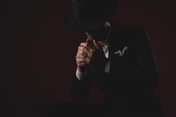mysterious young man lighting cigarette on black background