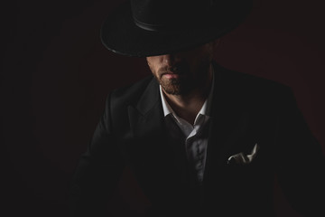 close up of mysterious young man in tuxedo on black background