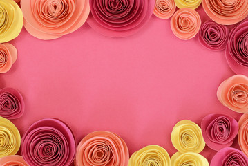 Pastel pink, magenta and yellow paper rose flat lay background with flowers around the endges and empty copy space in middle