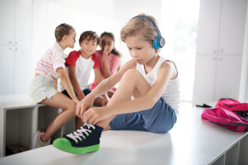 Blonde boy lacing sneakers while classmates gossiping