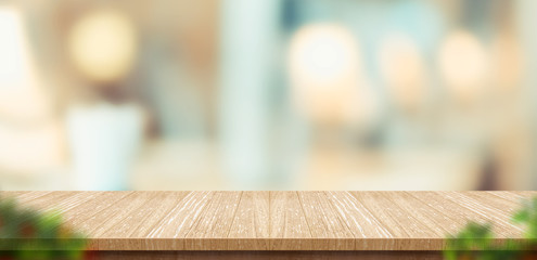 wood table and blurred leaf foreground in restaurant with bokeh background. product display...