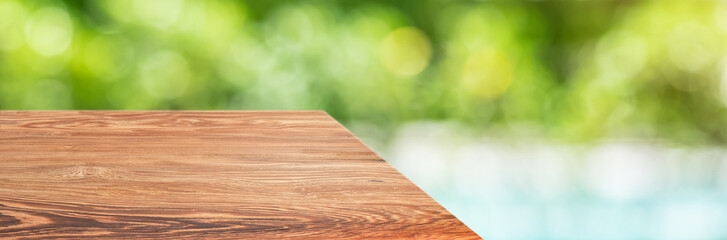 wood table top product display background with blur nature garden and swimming pool.perspective wooden kitchen counter with green leaf and sunlight.Banner mockup presentation