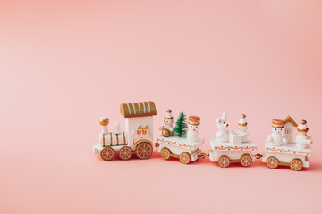 holiday concept.  Christmas and New Year.  postcard.  small toy miniature train with Santa, snowman, Christmas tree, on a pink background in isolation