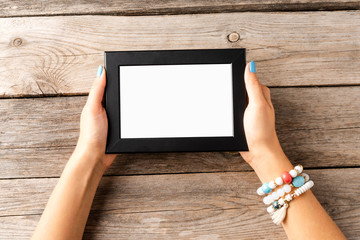 Woman's hand holding empty photo frame on wooden table. Top view