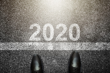 Businessman is looking down at his feet on a Asphalt road with 2020 number painted on the surface.Concept for success in the future goal and passing time. Happy new year