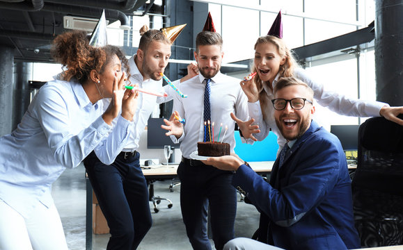 Business team celebrating a birthday of collegue in the modern office