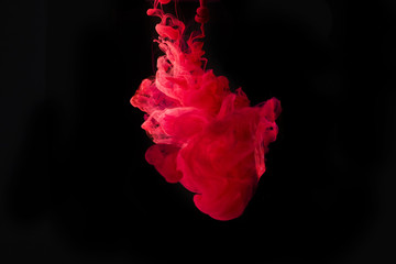 Studio shot of colored ink in water isolated on black background